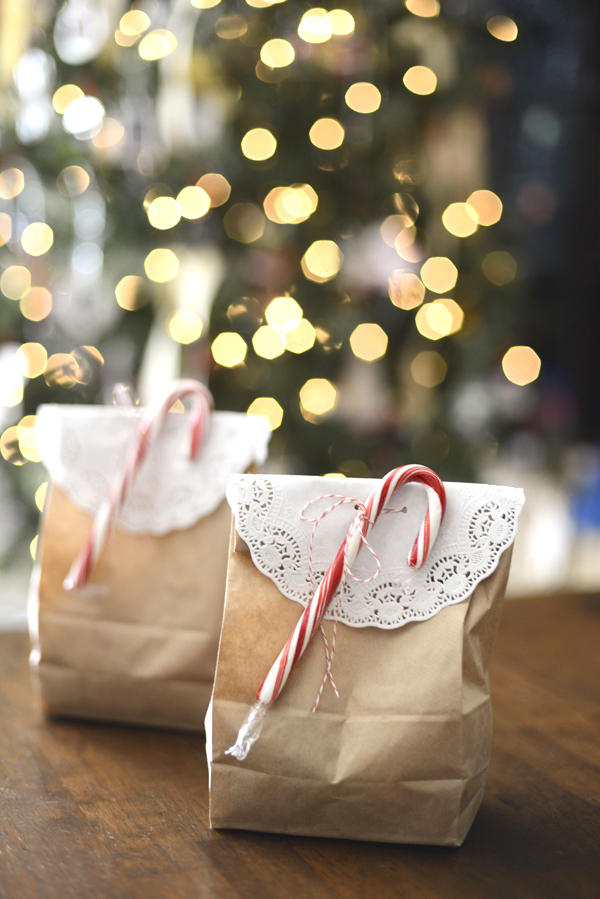Simple Christmas gift wrapping idea using a brown paper bag, a doily, and a candy cane.